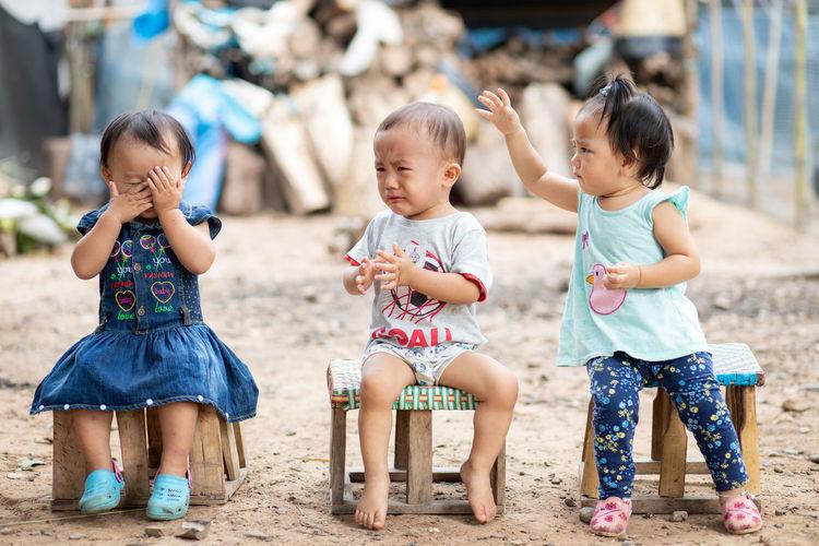 Full length of children sitting outdoors