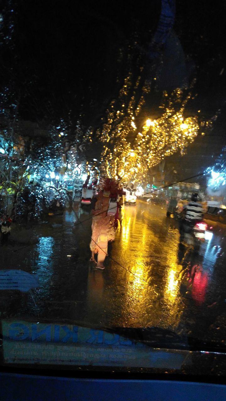 illuminated, night, water, land vehicle, car, wet, transportation, real people, men, tree, lifestyles, outdoors, nature, people