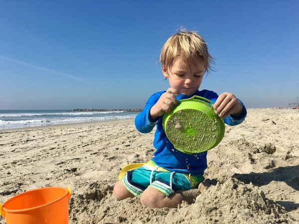 Enjoy The New Normal Childhood Sand Beach One Person Boys Sea Blue Toddler having a beach day Full Length Males  Child One Boy Only Children Only Leisure Activity Sky Sand Pail And Shovel Real People Water Looking Down Outdoors Uniqueness The Portraitist - 2017 EyeEm Awards California Dreamin