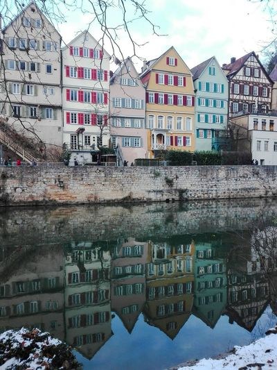 the beautiful colorful houses of old Tübingen reflecting in the water Tübingen Tuebingen Baden Württemberg Façade Beautiful Colorful Reflecting Mirroring Water River Embankment Historic Building Exterior Water Architecture Built Structure Reflection Mountain Day Outdoors Snow No People Sky City Cityscape