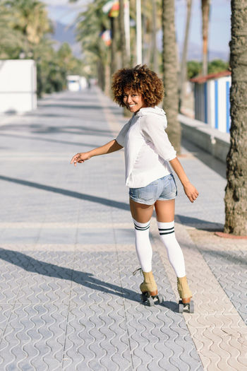 Smiling black woman on roller skates riding outdoors on beach promenade with palm trees. Smiling girl with afro hairstyle rollerblading on sunny day. Afro Hair Happiness Africa Beautiful Woman Curly Hair Hairstyle Happiness Leisure Activity Lifestyles One Person Outdoors People Real People Rear View Rollerblading Rollerskating Skates Smile Smiling Sport Clothes Sports Young Adult Young Women