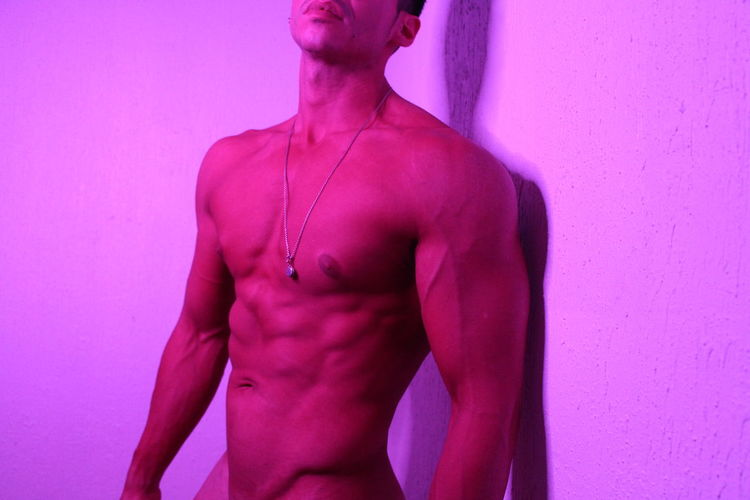 Midsection of shirtless man standing against pink wall