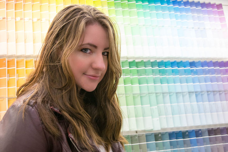 Portrait of young woman by colorful color swatches at store