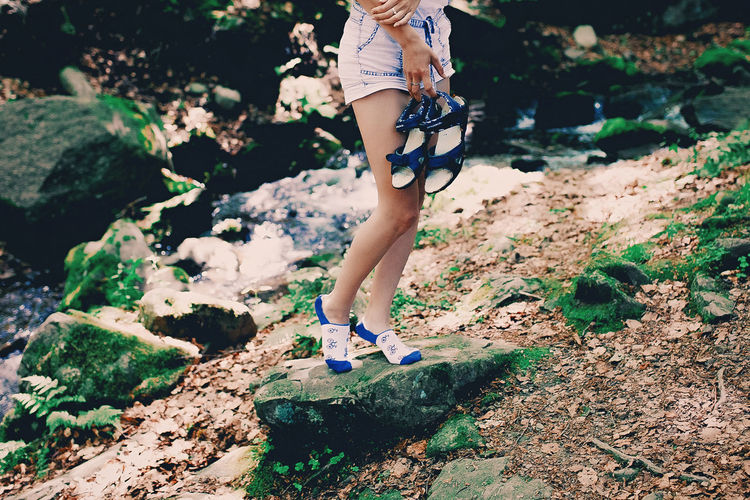 Low section of woman walking on rock