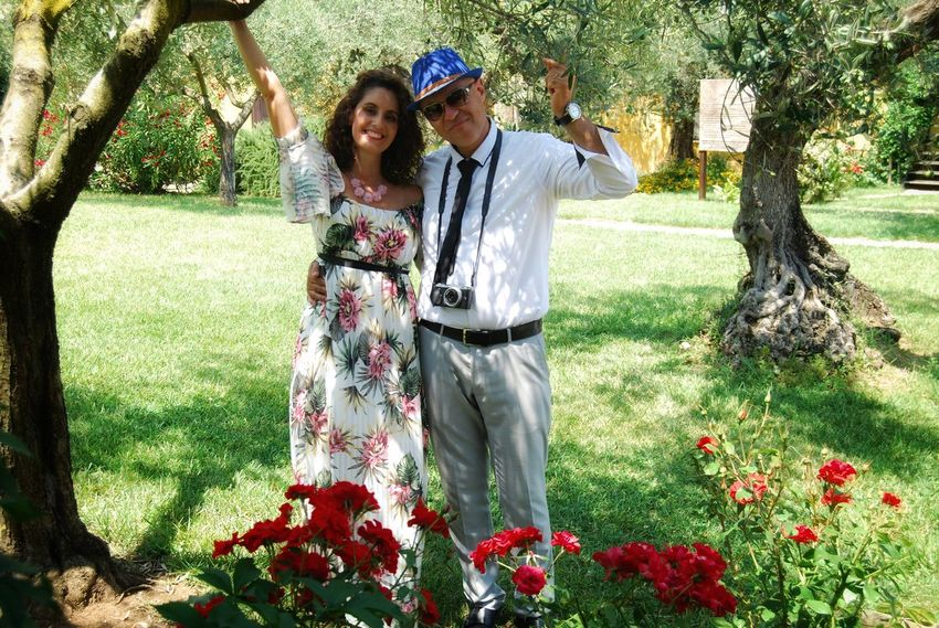 couple in love under an olive tree Arms Raised Couple - Relationship Emotion Flower Flowering Plant Front View Grass Happiness Human Arm Human Limb Limb Men Nature Outdoors Plant Portrait Smiling Standing Three Quarter Length Togetherness Tree Two People Women Young Adult Young Women