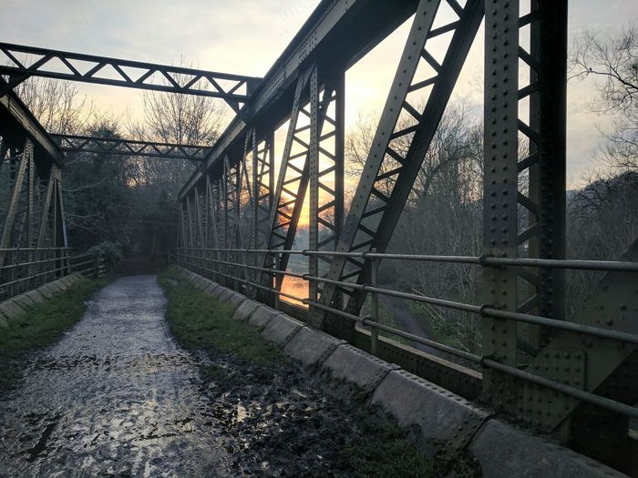 Metallic bridge over river against sky during sunset
