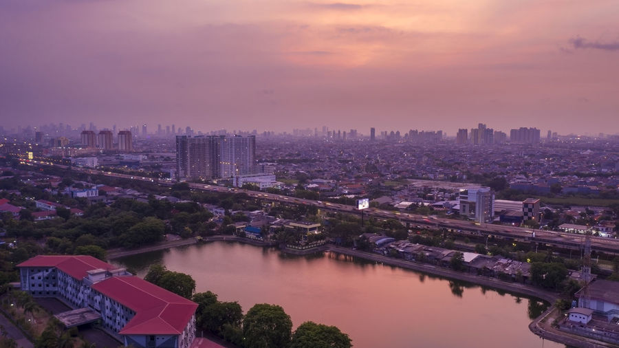 High Angle View Of River Amidst Buildings Against Sky At Sunset
