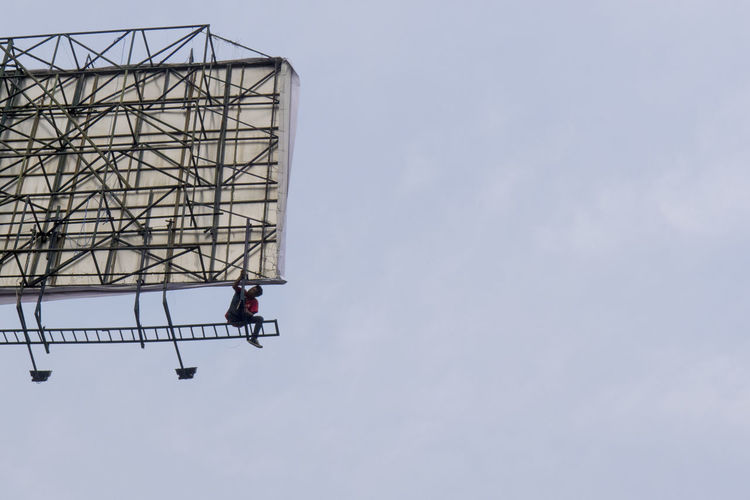 Low Angle View Of Man Working On Billboard Against Sky