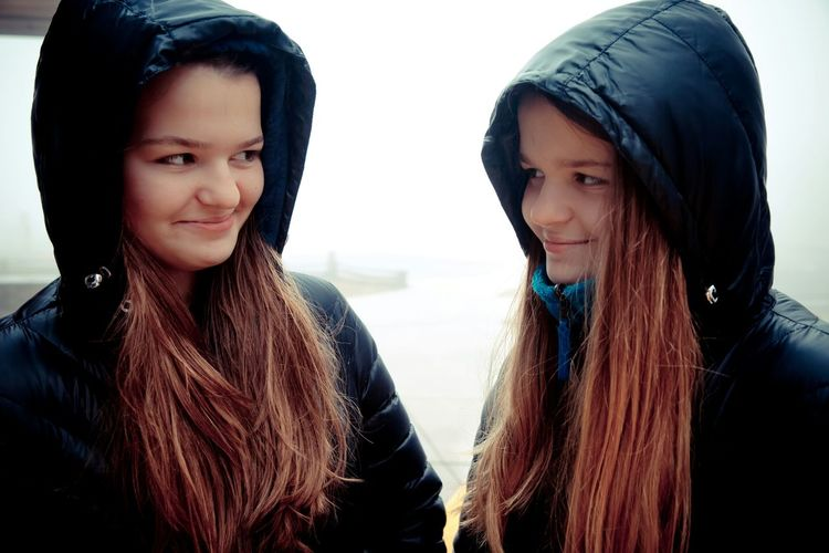 Twins wearing hood while looking at each other