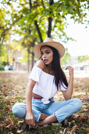 One Person Leisure Activity Sitting Hat Real People Clothing Young Women Lifestyles Young Adult Full Length Casual Clothing Plant Front View Portrait Women Day Long Hair Nature Hairstyle Hair Beautiful Woman Sun Hat Outdoors Teenager Contemplation