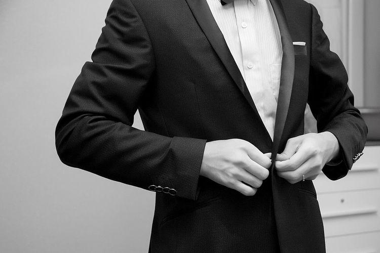 Midsection of businessman adjusting suit