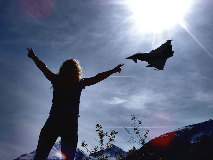 Top gun in the alps Arms Outstretched Cloud - Sky Eurofighter Freedom Human Arm Low Angle View Military Airplane One Person Outdoors Real People Silhouette Sky Sun Sunlight Women