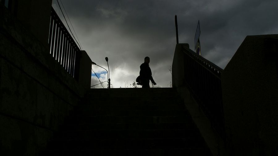 Low angle view of silhouette man on steps against sky
