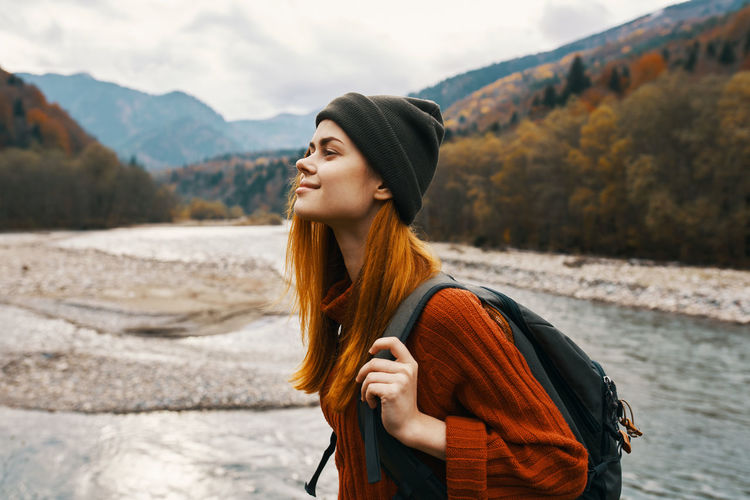 Young woman looking away while standing on mountain
