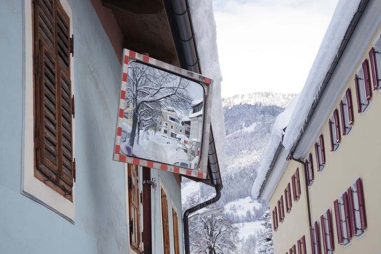 Text on snow covered buildings against mountain