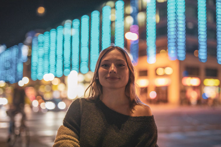Portrait of woman standing on illuminated street in city at night