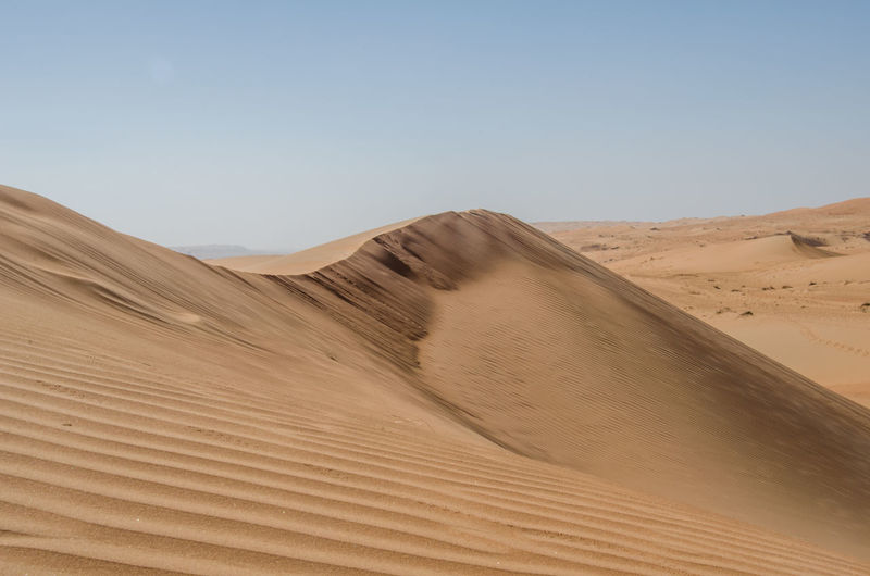 Desert in Oman, Wahiba Sands Arid Climate Atmospheric Beauty In Nature Clear Sky Climate Day Desert Environment Extreme Terrain Land Landscape Nature No People Non-urban Scene Outdoors Remote Sand Sand Dune Scenics - Nature Sky Tranquil Scene Tranquility