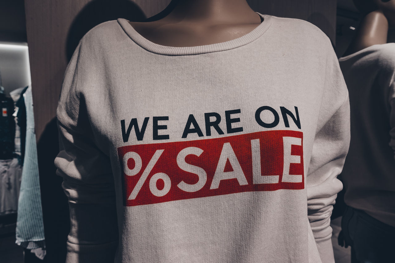 text, midsection, western script, communication, real people, standing, focus on foreground, one person, sign, red, lifestyles, casual clothing, women, adult, day, front view, clothing, indoors, close-up, message