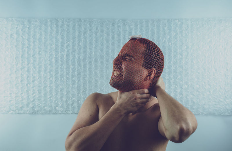 Man Strangling Neck With Netting Against Wall