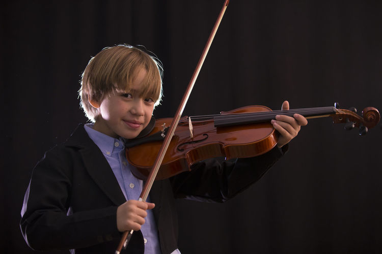 Boy Playing Violin While Standing Against Black Background