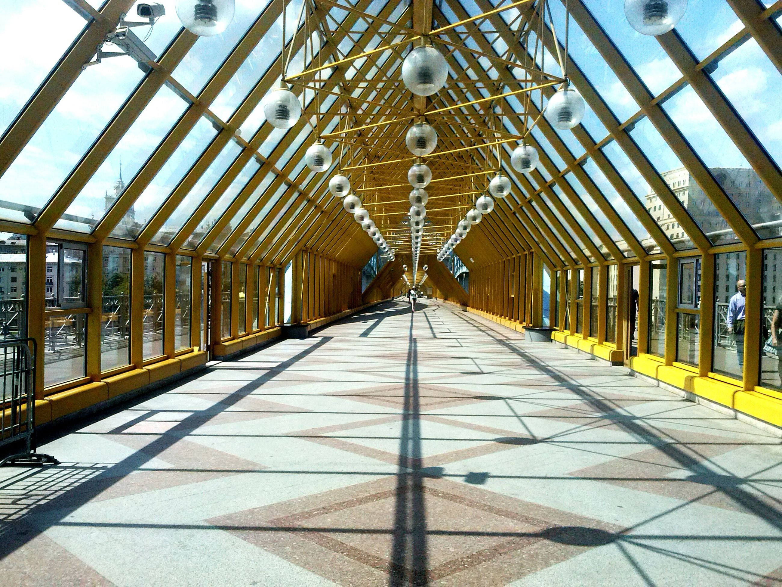 ceiling, indoors, architecture, the way forward, built structure, diminishing perspective, lighting equipment, vanishing point, in a row, corridor, pattern, flooring, empty, illuminated, incidental people, tiled floor, architectural column, architectural feature, walkway, design