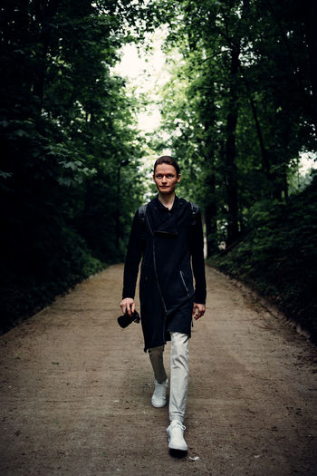 Full length portrait of young man walking on footpath in forest
