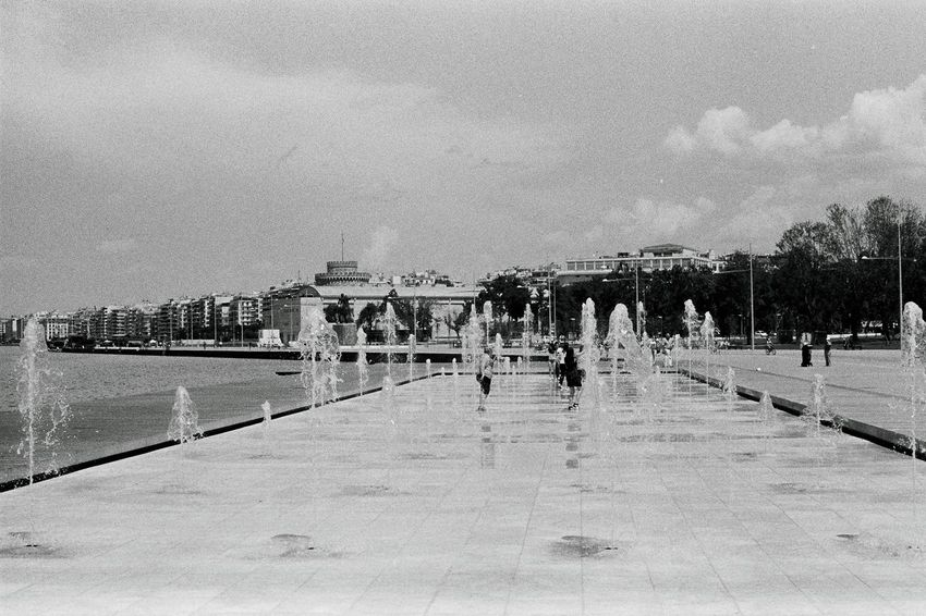 Analogue Photography Children City Life Having Fun Playing With Water Built Structure Children Playing City Cloud - Sky Day Enjoying Summer Happy Memories Hot Days Of Summer Large Group Of People Outdoors People Sky Water Water Fountain