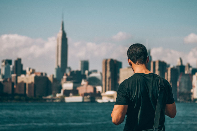 Rear View Of Man Standing By Sea Against Manhattan