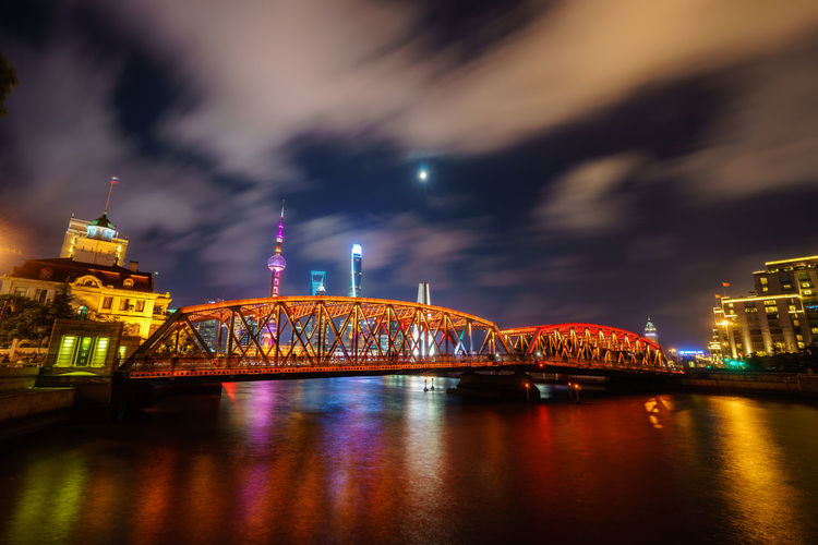 Low Angle View Of Illuminated Oriental Pearl Tower And Bridge In Front Of River Against Sky In City