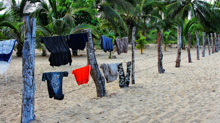 Clothes drying on wooden post at beach