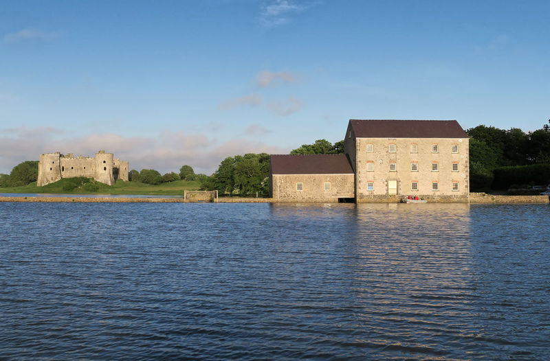 Carew Mill with Carew Castle in the background ..seen from the river view at highest tide Carewcastle Cleddau Wales Architecture Building Exterior Built Structure Mill No People Old Pembrokeshire River Scenics - Nature Sky The Past Water Waterfront