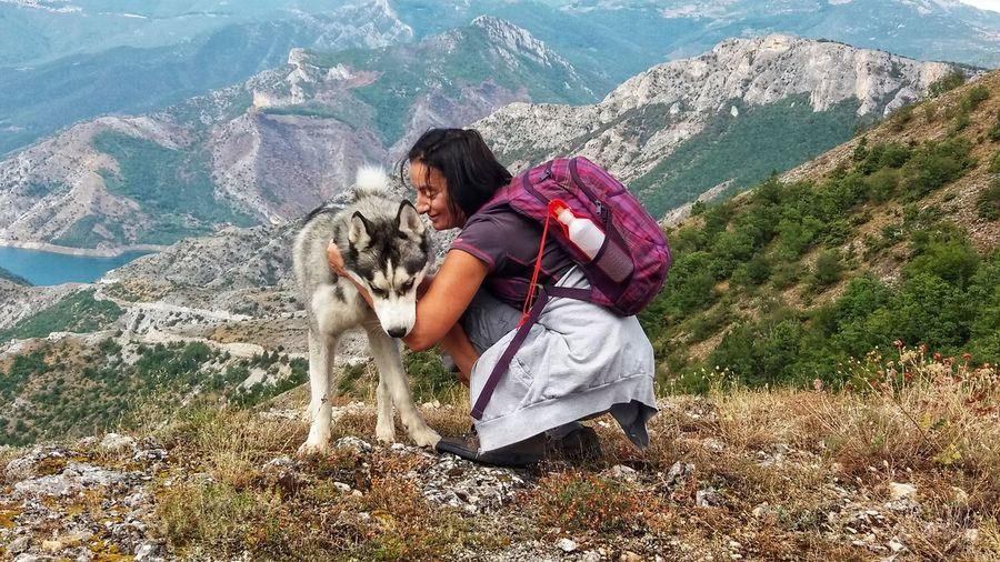 Backpacker with dog on mountain