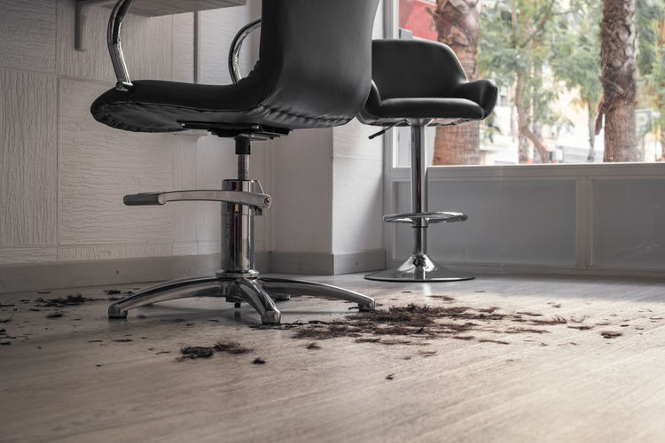 Close-up of hair fallen on floor by chairs at salon