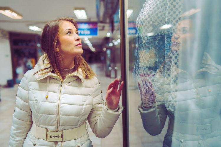 Beautiful woman looking retail display of store