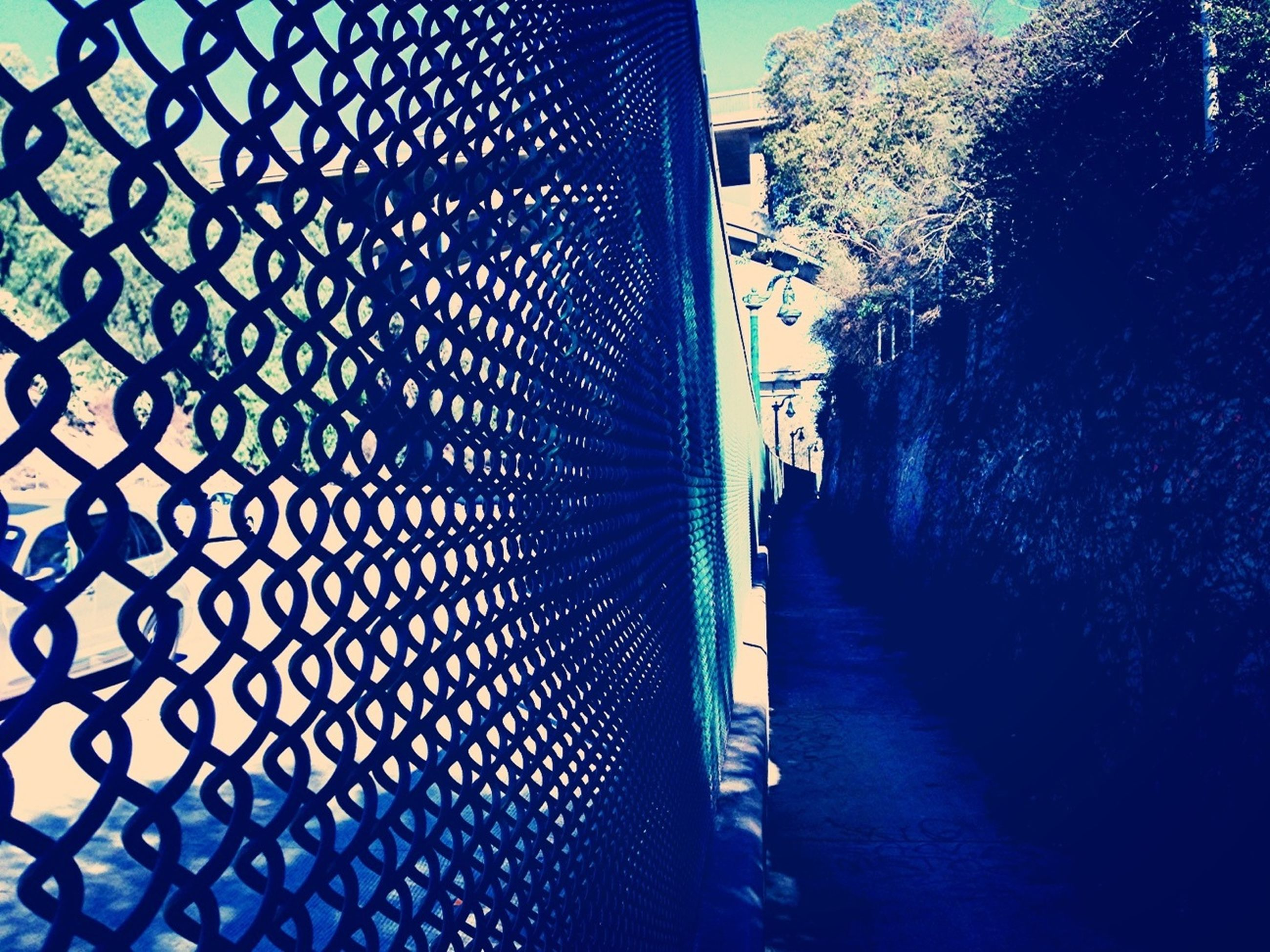 built structure, architecture, building exterior, transportation, city, railing, the way forward, protection, day, bicycle, street, metal, sunlight, sidewalk, fence, wall - building feature, safety, outdoors, incidental people, chainlink fence