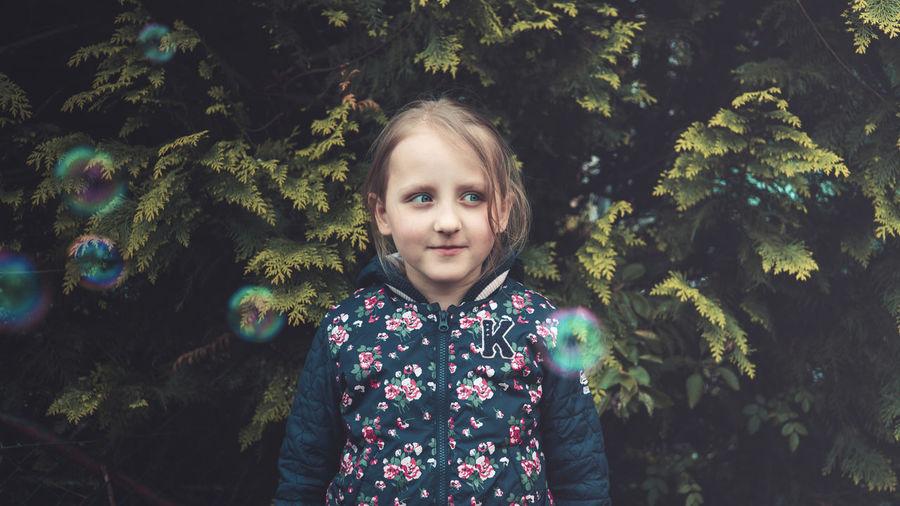 Portrait Of Girl Standing Amidst Bubbles Against Plants