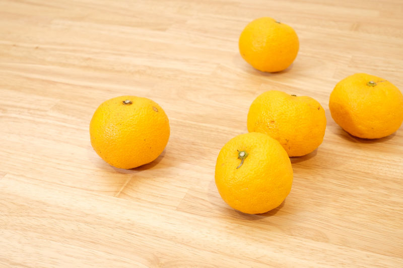 Citron, Japanese YUZU Fruit Citrus Fruit Healthy Eating Wellbeing Food Food And Drink Freshness Still Life Indoors  Close-up Orange Color Orange Orange - Fruit No People Yellow Citron Yuzu Table Wood - Material High Angle View Group Of Objects Focus On Foreground Wood Grain