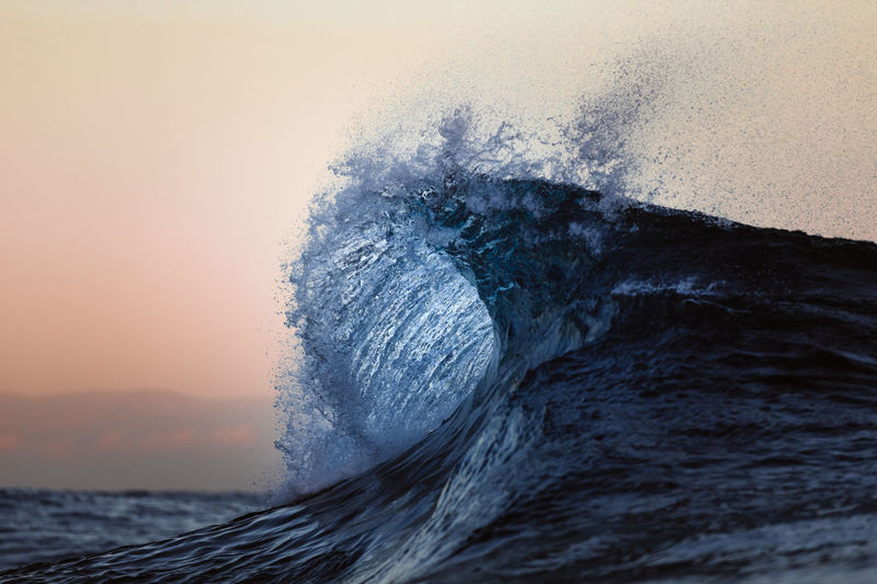 Close-up of sea waves splashing against sky during sunset