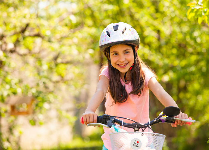 Cute girl riding bicycle outdoors
