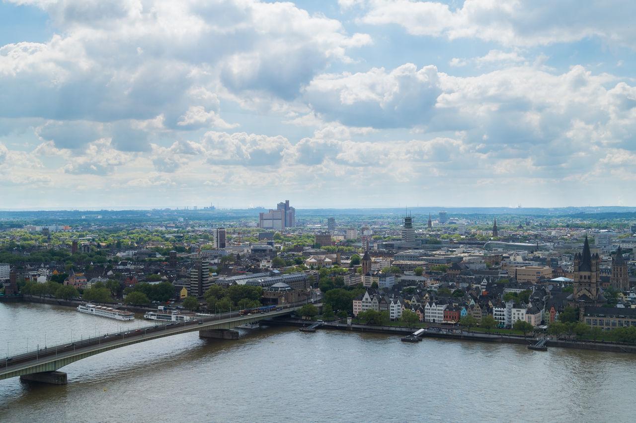 Deutz Suspension Bridge Over Rhine River By City Against Cloudy Sky