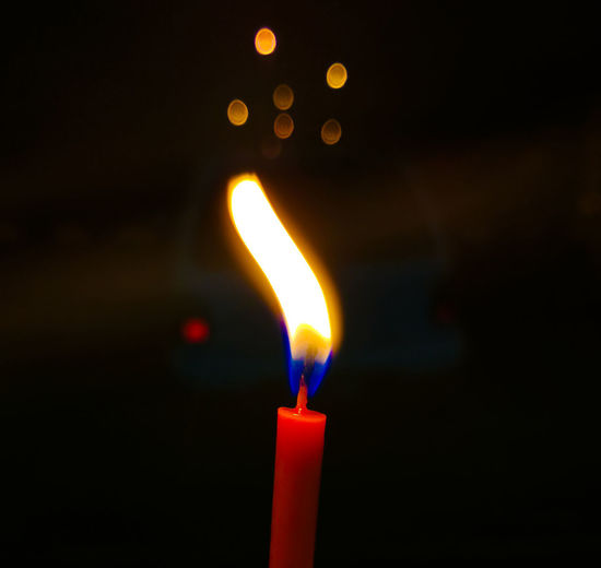 Close-up of lit candle in darkroom