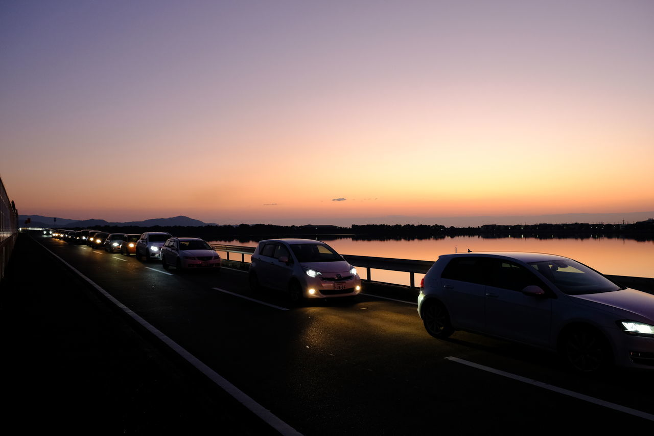transportation, car, mode of transportation, motor vehicle, sky, land vehicle, sunset, road, nature, copy space, no people, clear sky, motion, on the move, city, travel, orange color, street, outdoors, dusk, road trip, multiple lane highway