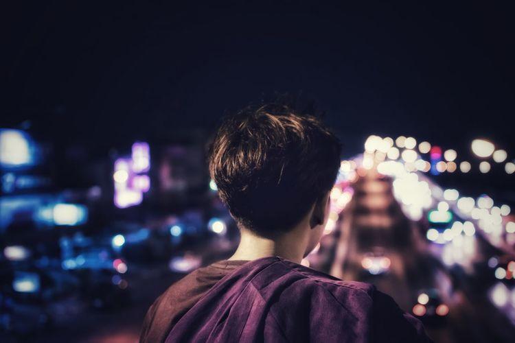 Rear view of man at illuminated amusement park