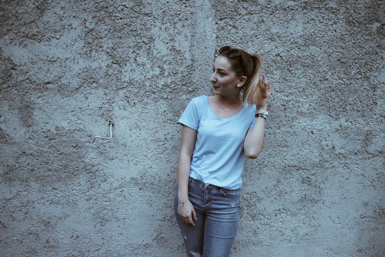 Thoughtful Young Woman Standing Against Wall