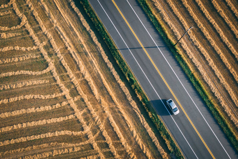 Aerial view of car on highway commuting to work or on a road trip Automobile Commuting Farm Road Aerial View Automotive Car High Angle View Highway Mode Of Transportation Road Road Trip Rural Scene Transportation It's About The Journey