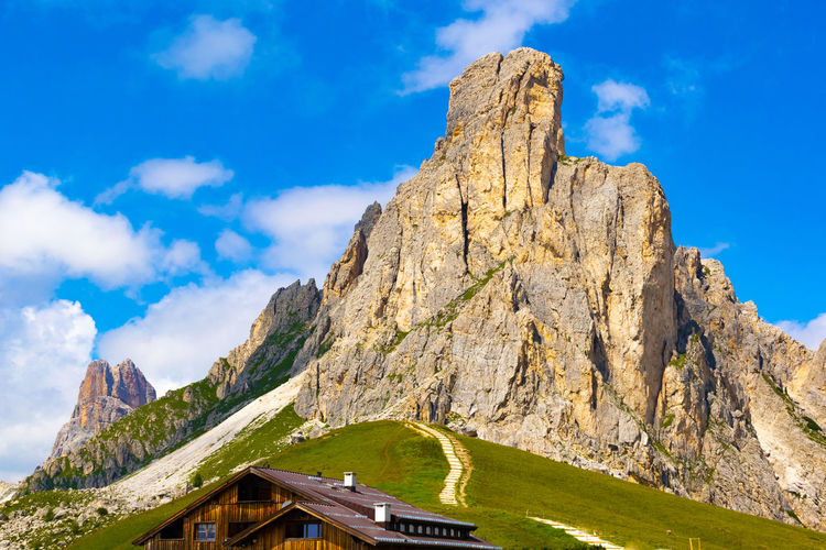 Low angle view of dolomites mountains against blue sky