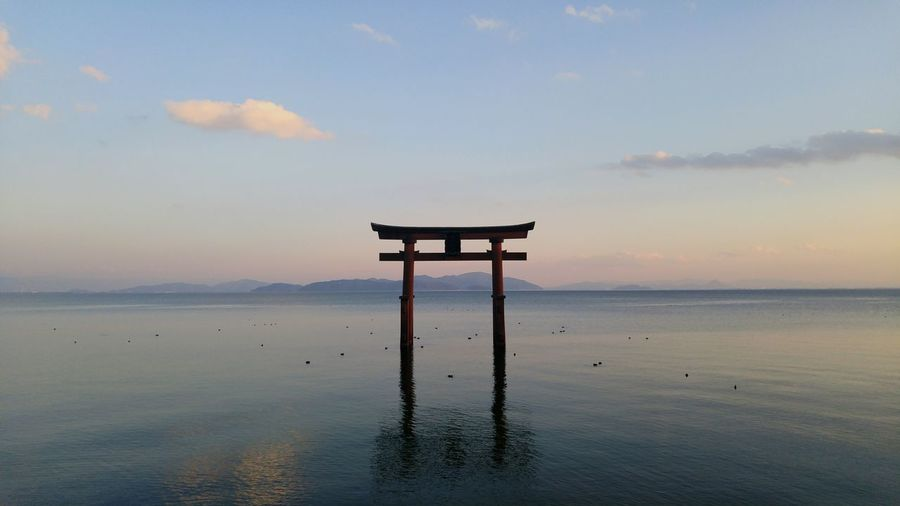 Torii Gate In Calm Lake Against Sky During Sunset