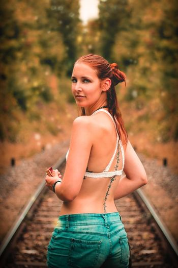 Portrait of a beautiful young woman standing on railroad track