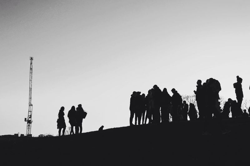 People silhouetted against clear sky