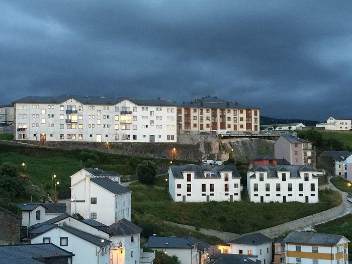 Buildings against cloudy sky at dusk